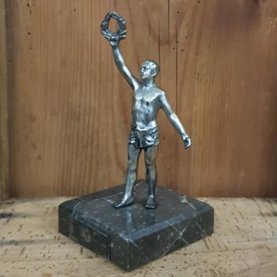 Soška trofej na mramorovém podstavci
